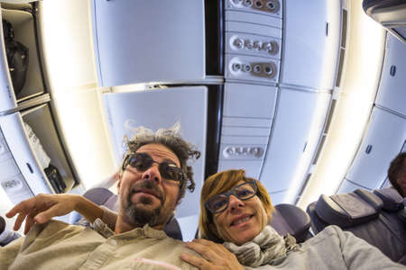 fish eye: Cheerful adult caucasian couple taking selfie inside plane. Fish eye view from below. Concept of people traveling, natural light.
