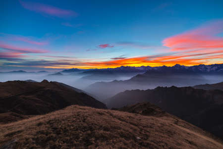 Colorful sunlight behind majestic mountain peaks of the Italian - French Alps, viewed from distant. Fog and mist covering the valleys below, autumnal landscape, cold feeling.
