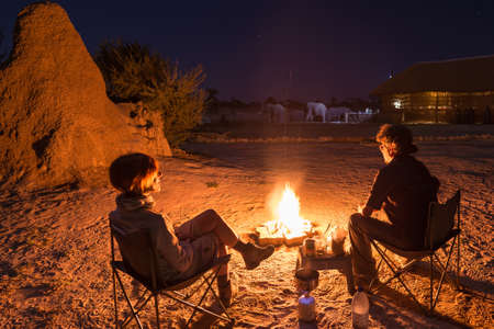 Couple sitting at burning camp fire in the night. Camping in the desert with wild elephants in background. Summer adventures and exploration in the african National Parks. Camping stove and gas burner.