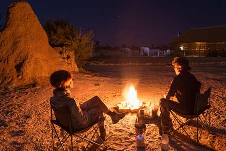 Paar sitzt am Lagerfeuer in der Nacht brennen. Camping in der Wüste mit wilden Elefanten im Hintergrund. Sommer Abenteuer und Exploration in den afrikanischen Nationalparks. Campingkocher und Gasbrenner. Standard-Bild - 70173945