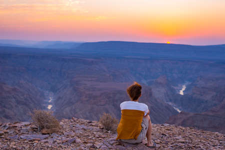 Rear view of tourist looking at expansive view over the Fish River Canyon, scenic travel destination in Southern Namibia. Ultra wide angle view from above.