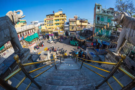Udaipur, India - January 29, 2017: Crowd and traffic in the enchanting Udaipur, famous travel destination in Rajasthan, India. Fisheye view from the staircase above at Jagdish hindu temple.