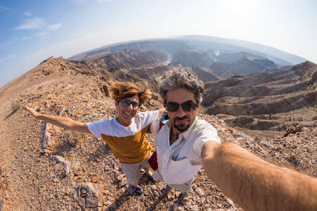 Couple taking selfie at the Fish River Canyon, scenic travel destination in Southern Namibia. Fisheye view from above in backlight.