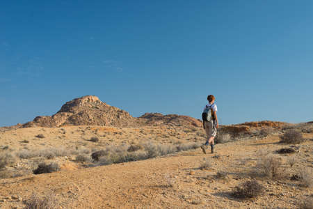 One person hiking in the Namib desert, Namib Naukluft National Park, Namibia. Adventure and exploration in Africa. Clear blue sky.