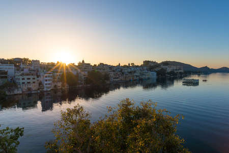 Udaipur cityscape at sunrise. The majestic city palace on Lake Pichola, travel destination in Rajasthan, India.   Stock Photo
