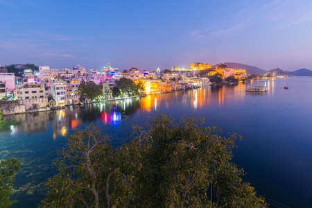 Glowing cityscape at Udaipur at dusk. The majestic city palace reflecting lights on Lake Pichola, travel destination in Rajasthan, India
