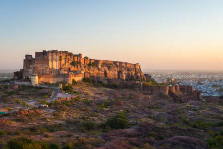 Cityscape at Jodhpur at dusk. The majestic fort perched on top dominating the blue town. Scenic travel destination and famous tourist attraction in Rajasthan, India.