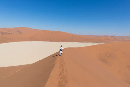 Tourist walking on the scenic dunes of Sossusvlei, Namib desert, Namib Naukluft National Park, Namibia. Adventure and exploration in Africa.