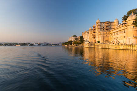 Udaipur cityscape at sunset. The majestic city palace on Lake Pichola, travel destination in Rajasthan, India Editorial
