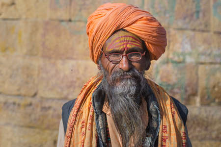 Jaisalmer, India - March 2, 2017: Sadhu portrait and close up at Jaisalmer, Rajasthan, India. The hindu spiritual guide and priest, against ancient stone wall.