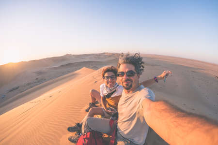 Adult couple taking selfie on sand dunes in the Namib desert, Namib Naukluft National Park, main travel destination in Namibia, Africa. Fisheye view in backlight, toned image. Imagens