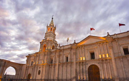 Stunning colorful sky and clouds at dusk in Arequipa, famous travel destination and landmark in Peru. Wide angle view from below of the colonial Cathedral. Panoramic frame. Stock Photo