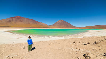 Tourist looking at the stunning landscape of Laguna Verde (eng. Green Lagoon), a frozen salt lake on the way to the Uyuni Salt Flat, Bolivia. Snowcapped Licancabur Volcano, 5920 m, in the background. Stock Photo