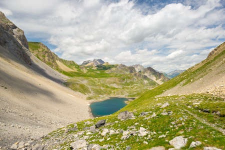 morphology: High altitude blue lake in idyllic uncontaminated environment once covered by glaciers. Summer adventures and exploration on the Italian French Alps. Expansive view from above, clear blue sky.