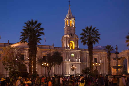 Arequipa, Peru - August 15, 2015: People on the main square, Plaza de Armas, of Arequipa, famous travel destination and landmark in Peru. The majestic Cathedral in the background. Night view.