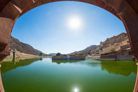 Framed view of the honey toned impressive Amber Fort, famous tourist attraction at Jaipur, Rajasthan, India. Backlight, clear blue sky, fish eye and ultra wide angle view. Stock Photo