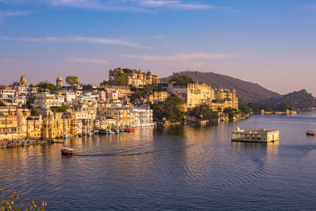 The famous city palace on Lake Pichola reflecting sunset light. Udaipur, travel destination and tourist attraction in Rajasthan, India