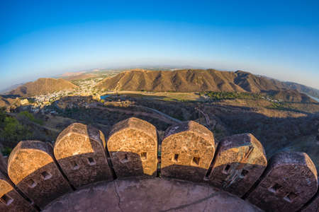 The impressive landscape and cityscape from above at Amber Fort, famous travel destination in Jaipur, Rajasthan, India. Fish eye and ultra wide angle view from the fort tower.