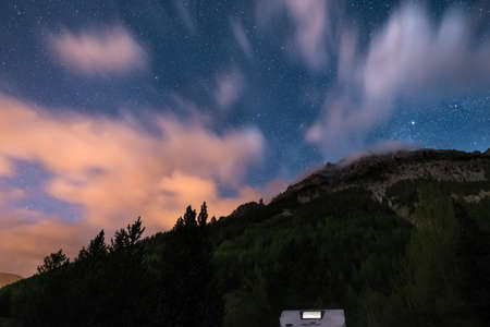 Camper van under moonlight, starry sky and blurred motion clouds on the majestic Alps. Outdoor activities and adventure into the wild.