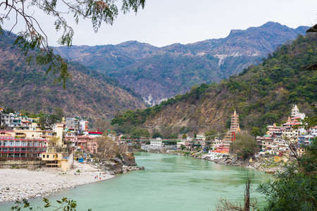 Rishikesh, holy town and travel destination in India. The Ganges River flowing between mountain from the Himalayas Stock Photo
