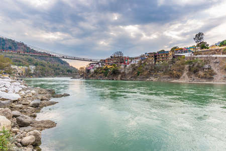 Dramatic sky at Rishikesh, holy town and travel destination in India. Colorful sky and clouds reflecting over the Ganges River. Stock Photo