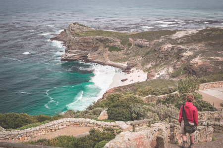 Tourist hiking at Cape Point, looking at view of Cape of Good Hope and Dias Beach, travel destination in South Africa. Table Mountain National Park, Cape Peninsula. Toned image.