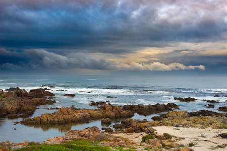 Rocky coast line on the ocean at De Kelders, South Africa, famous for whale watching. Winter season, cloudy and dramatic sky. Stock Photo