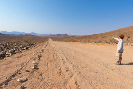 Tourist walking on 4x4 road crossing the colorful desert at Twyfelfontein, in the majestic Damaraland Brandberg, scenic travel destination in Namibia, Africa.