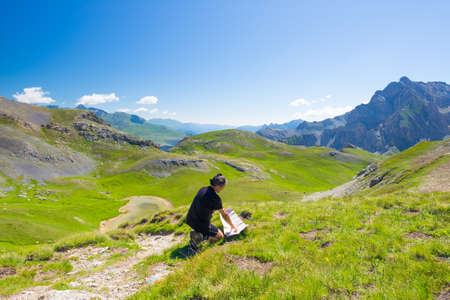 conquering adversity: Hiker reading trekking map while resting at panoramic mountain spot. Outdoors activities, summer adventures and exploration on the Italian French Alps. Expansive view from the top.