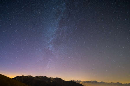 bardonecchia: The wonderful starry sky on Christmas time and the majestic high mountain range of the Italian French Alps, with glowing villages below and moonlight.