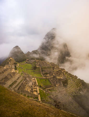 Machu Picchu illuminated by the first sunlight coming out from the opening clouds. The Incas city is the most visited travel destination in Peru. Mist, clouds and fog covering the valley.
