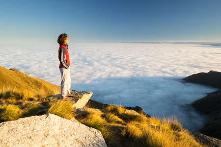 eco tourism: Female hiker reaching her goal at the mountain top and looking at majestic panoramic view of the italian western Alps with clouds on the valley below. Wide angle view at sunset.