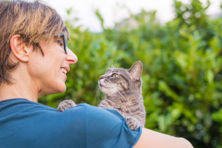 cuddled: Playful domestic cat held and cuddled by smiling woman with eyeglasses. Outdoor setting in green home garden. Shallow depth of field, focused on animal head. Toned image.
