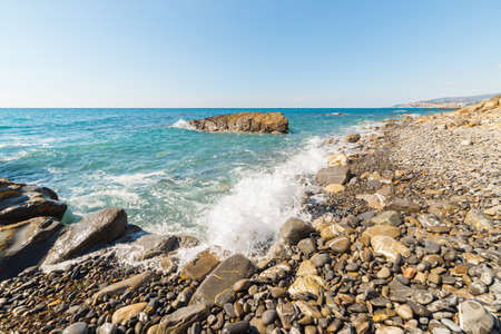 waves  pebble: Water waves breaking on gravels, pebbles and boulders of an empty beach in the harsh rocky coastline of Liguria, North Italy. Clear blue sky, wide angle view.