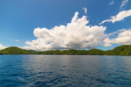 Rocky coastline of island spotted by islets and covered by dense lush green jungle in the colorful sea of the remote Togean Islands (or Togian Islands), Central Sulawesi, Indonesia.