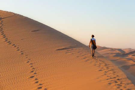 Toerist die op de schilderachtige duinen van Sossusvlei, Namib woestijn, Namib Naukluft National Park, Namibië. Middag licht. Avontuur en exploratie in Afrika. Stockfoto