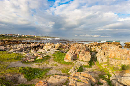 table mountain national park: Rocky coast line on the ocean at De Kelders, South Africa, famous for whale watching. Winter season, cloudy and dramatic sky. Stock Photo