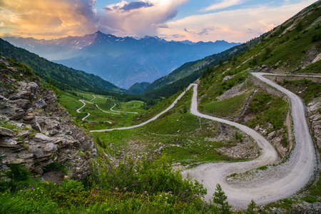 Dirt mountain road leading to high mountain pass in Italy (Colle delle Finestre). Expasive view at sunset, colorful dramatic sky, adventures in summer time, Italian Alps.
