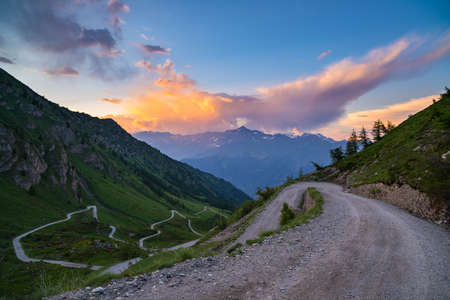 bardonecchia: Dirt mountain road leading to high mountain pass in Italy (Colle delle Finestre). Expasive view at sunset, colorful dramatic sky, adventures in summer time, Italian Alps.