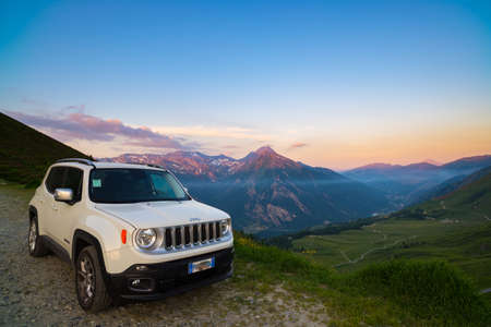 Colle di Finestre, Italy - June 22, 2017: White car parked on a dirt road at the panoramic view point of the Italian Alps from above. Colorful sky at sunset, mist on the valley below.
