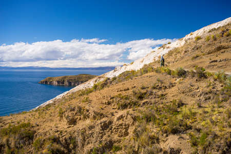 Backpacker exploring the incas majestic footpaths on Island of the Sun, Titicaca Lake, scenic travel destination in Bolivia. Travel adventures and vacations in the Americas.