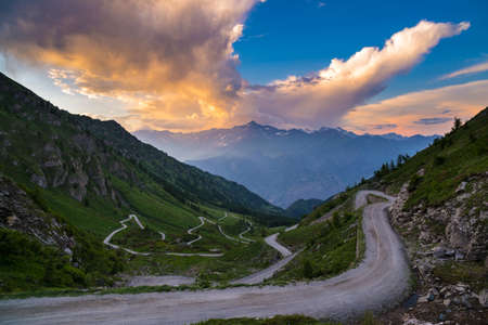 bardonecchia: Dirt mountain road leading to high mountain pass in Italy (Colle delle Finestre). Expansive view at sunset, colorful dramatic sky, adventures in summer time, Italian Alps. Stock Photo