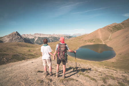 Couple of hiker on the mountain top looking at blue lake and mountain peaks. Summer adventures on the Alps. Wide angle view from above, toned image, vintage style. Stock Photo