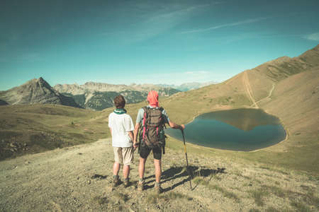 Couple of hiker on the mountain top looking at blue lake and mountain peaks. Summer adventures on the Alps. Wide angle view from above, toned image, vintage style. Editorial