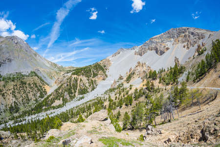 High altitude blue lake in idyllic uncontaminated environment once covered by glaciers. Summer adventures and exploration on the Italian French Alps. Expansive view from above, clear blue sky.