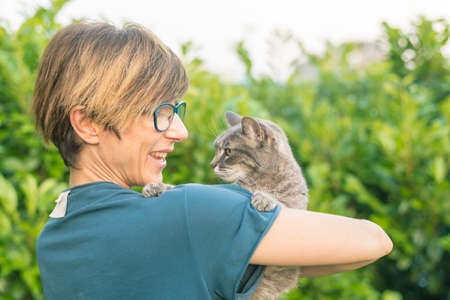 Playful domestic cat held and cuddled by smiling woman with eyeglasses. Outdoor setting in green home garden. Shallow depth of field, focused on animal head. Toned image.