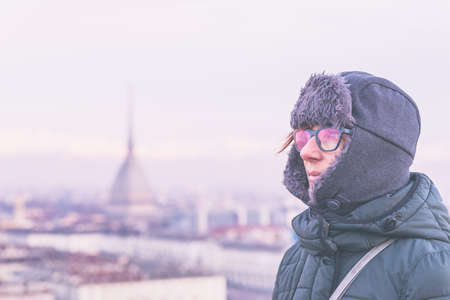 Tourist looking at panoramic view of Torino (Turin, Italy) from balcony above. Winter time, snowcapped Alps in the background. Selective focus, vintage style, toned image.