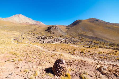 High altitude barren mountain range on the highlands of the Andes on the way to the famous Uyuni Salt Flat, among the most important travel destination in Bolivia. Abandoned old village in the plateau.