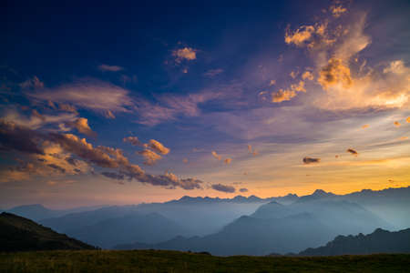 courmayeur: Colorful sunlight on the majestic mountain peaks, green pastures and foggy valleys of the Italian Alps. Golden cloudscape at sunset.