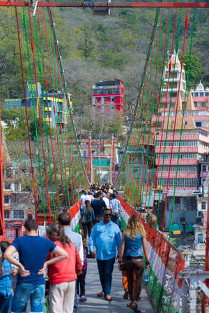 Rishikesh, India - March 10, 2017: People crossing the Ganges River on the suspension footbridge at Rishikesh, India, sacred town for Hindu religion and famous destination for Yoga classes. Editorial